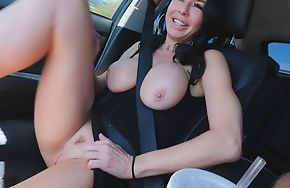 Raven haired mature in high heels masturbates in the car